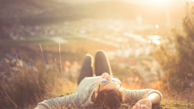 smiling person lying on a grassy hill on a sunny day